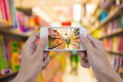 Frauen übergeben leeres intelligentes Mobiltelefon im Buchladen an halten sie Lizenzfreie Stockfotos