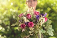 Frauen-Angebotblumenstrauß von frischen Blumen an der Kamera Stockbild