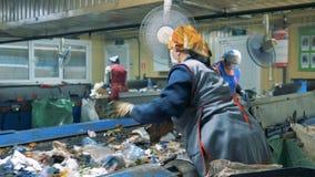Frauen arbeiten in einer Anlage und oben sortieren Abfall, Abschluss stock video footage