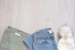 Frauen arbeiten Kleidung auf hölzernem Hintergrund um Flache angeredeter Blick der Lage Frau Strickjacke, Jeans und Pelzhut Besch stockbild
