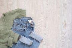 Frauen arbeiten Kleidung auf hölzernem Hintergrund um Flache angeredeter Blick der Lage Frau Strickjacke und Jeans Beschneidungsp stockfotografie