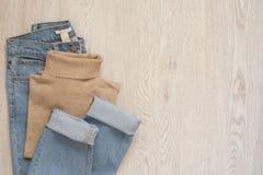 Frauen arbeiten Kleidung auf hölzernem Hintergrund um Flache Lage des weiblichen angeredeten Blickes Polobluse und -jeans Beschne lizenzfreies stockbild