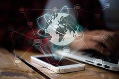 Frauen arbeiten an Laptop mit globalem und emailen Belichtung auf smartpho Lizenzfreies Stockfoto