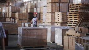 Frauen-Arbeiter im Sturzhelm, der Verpackungsfeuerfeste ziegel mit Werkstattschienenportalkran transportiert stock footage