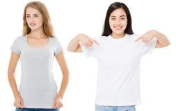 Frauen asiatisch und Kaukasier im leeren Schablonent-shirt lokalisiert auf weißem Hintergrund Girlsl in den T-Shirts mit Kopienra lizenzfreies stockbild