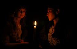 Frauen auf jeder Seite der Kerze in der Dunkelheit Stockfotos
