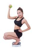Frauen auf Skala zujubelnd für das Erzielen ihres Gewichtsverlustziels Lizenzfreie Stockbilder
