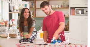 Frauen-aufpassendes Mann-bügelndes Hemd in der Küche Lizenzfreie Stockfotos