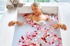 Frauen-Badekurort-Blumen-Bad aromatherapy Entspannungsrose bathtub schönheit lizenzfreie stockbilder