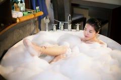 Frauen badeten in eine Badewanne mit Glück Lizenzfreie Stockfotos