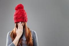 Frauen-Bedeckungs-Augen mit roter Mütze Stockfotos