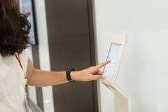 Frauen bedrängen Zahl auf Zugriffskontrolle, um Aufzugsboden zu entriegeln und den Boden zu wählen Stockfotografie