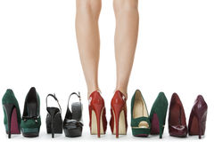 Frauen-Beine in den roten Schuhen zwischen anderen hohen Absätzen Lizenzfreies Stockbild