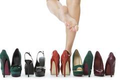 Frauen-Beine in den roten Schuhen zwischen anderen hohen Absätzen Stockbild