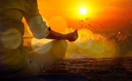 Frauen-übendes Yoga durch das Meer bei Sonnenuntergang Lizenzfreie Stockfotografie