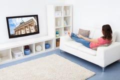 Frauen-überwachendes Fernsehen Lizenzfreie Stockfotografie