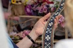 Frauen betrachtet handgemachten gesponnenen Gurt Dekorativer Latvian ist stockbild