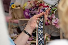 Frauen betrachtet handgemachten gesponnenen Gurt Dekorativer Latvian ist stockfotografie