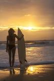 Frauen-Bikini-Surfer u. Surfbrett-Sonnenuntergang-Strand Stockfotografie