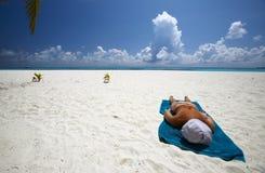 Frauen bräunt sich auf dem sandigen Strand Stockfoto