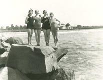 Frauen in den Badeanzügen, die auf Felsen aufwerfen stockbild