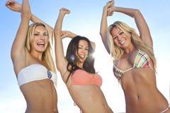 Frauen in den Bikinis, die auf sonnigen Strand tanzen Stockfoto