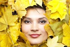 Frauen in den gelben Herbstblättern. Lizenzfreie Stockfotos