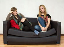Frauen in den hellen Kleidern sitzen auf dem schwarzen Sofa Stockfoto
