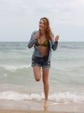 Frauen in den Jeans, die auf den Strand laufen Lizenzfreies Stockfoto