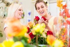 Frauen in den kaufenden Rosen des Blumenspeichers Lizenzfreies Stockfoto