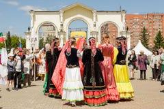 Frauen in den nationalen Kostümen tanzen in einen Kreis, Händchenhalten stockfoto