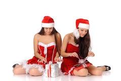Frauen in den Weihnachtskostümen öffnen Geschenke Lizenzfreies Stockfoto