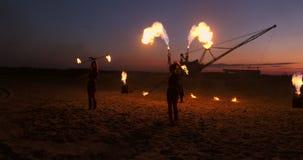 Frauen der Feuershow drei in ihren Händen verdrehen brennende Stangen und Fans im Sand mit einem Mann mit zwei Flammenwerfern in  stock video footage