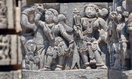 Frauen in der Trachtenmodeart auf Entlastung des des 12. Jahrhundertshoysaleshwara-Tempels in Halebidu, Karnataka-Staat Stockbilder