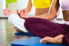 Frauen in der Turnhalle, die Yoga tut, trainieren für Eignung Stockbild
