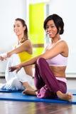 Frauen in der Turnhalle, die Yoga tut, trainieren für Eignung Stockfotografie