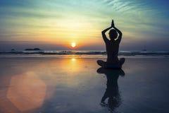 Frauen in der Yogameditation werfen bei erstaunlichem Sonnenuntergang auf Lizenzfreie Stockfotos