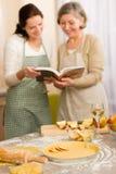 Frauen des Apfelkuchenrezepts zwei, die Kochbuch schauen Stockbild