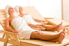 Frauen des Schönheitsbadekurort-Raumes zwei entspannen sich Sonnebetten Stockbilder