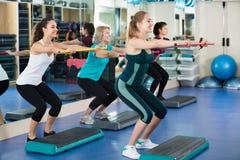 Frauen, die auf aerober Schrittplattform ausarbeiten Lizenzfreies Stockbild