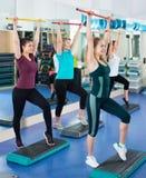 Frauen, die auf aerober Schrittplattform in der modernen Turnhalle ausarbeiten Lizenzfreie Stockfotografie