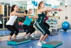Frauen, die auf aerober Schrittplattform in der modernen Turnhalle ausarbeiten Stockbild