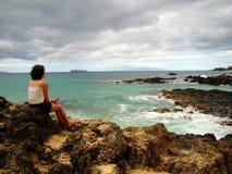 Frauen, die auf dem felsigen Strand, Maui, Hawaii sitzen lizenzfreie stockfotos