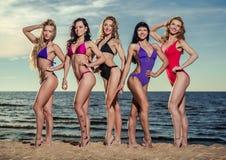 Frauen, die auf dem Strand aufwerfen Stockfotos