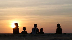 Frauen, die auf dem Strand bei Sonnenuntergang, mit dem Leuteüberschreiten meditieren stock video footage
