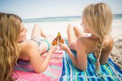 Frauen, die auf dem Strand mit Bierflasche liegen Lizenzfreies Stockbild