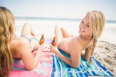 Frauen, die auf dem Strand mit Bierflasche liegen Stockbilder