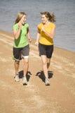 Frauen, die auf dem Strandlachen laufen Stockfoto