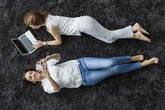 Frauen, die auf dem Teppich sich entspannen Stockfoto