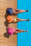 Frauen, die auf der Plattform durch den Swimmingpool reaxing sind Stockfoto